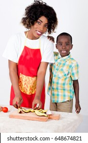 Young happy woman carving avocado on a piece of wood poses with her child standing near her and looking at the camera.
