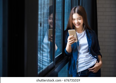 young happy woman in casual clothes standing at large window listening to music on her phone, young and modern lifestyle concept in using modern technology in their life