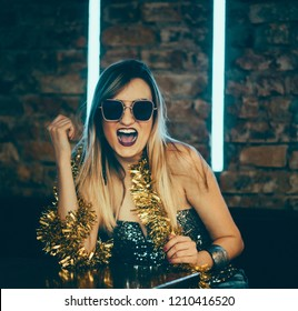 Young happy woman celebrating new year eve in night bar restaurant. Disco night lights and confetti. Beatiful lady clubber in nightclub having fun. Hipster girl at celebration luxury party.