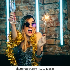 Young happy woman celebrating new year eve drinking champagne with fireworks. Lady clubber in nightclub having fun. Hipster girl at celebration luxury party.