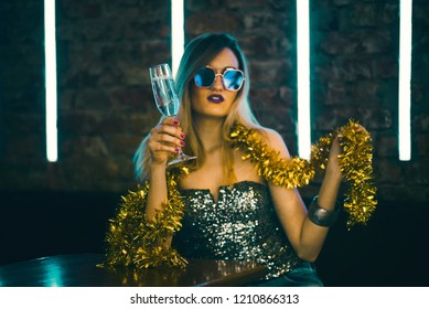 Young happy woman celebrating new year eve drinking champagne. Night lights and confetti. Lady clubber in nightclub having fun. Hipster girl at celebration luxury party.