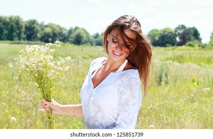 Young happy woman with chamomile bouquet