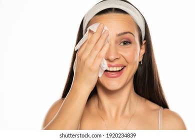 young happy woman cleaning her face with wet tissue on white background