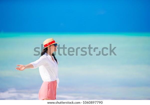 Young happy woman with coconut in swimsuit on white beach