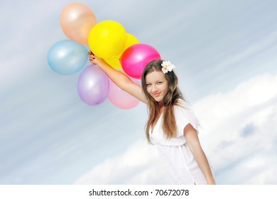young happy woman with colorful balloons on sky background