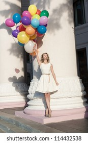Young happy woman with colorful latex balloons keeping her dress, urban scene, outdoors