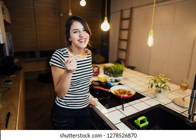 Young happy woman cooking a healthy meal in home kitchen.Making dinner on kitchen island standing by induction hob.Preparing fresh lunch,enjoying spice aromas.Eating in.Passion for cooking.Healthy