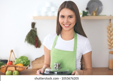 Young happy woman cooking in the kitchen. Healthy meal, lifestyle and culinary concept