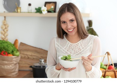 Young happy woman cooking in the kitchen. Healthy meal, lifestyle and culinary concepts. Good morning begins with fresh salad