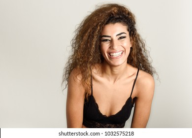 Young happy woman with curly hairstyle laughing. Studio shot.