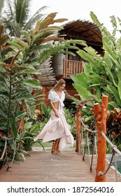 Young happy woman dancing in summer  dress on old wooden bridge in Ubud, Bali, wooden eco bungalow on background. Tropical travel in Indonesia