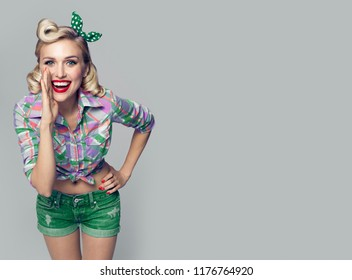 Young happy woman, dressed in pin-up style. Caucasian blond model posing in retro fashion and vintage concept studio shoot, on grey background. Copy space area for advertise, slogan or text message.