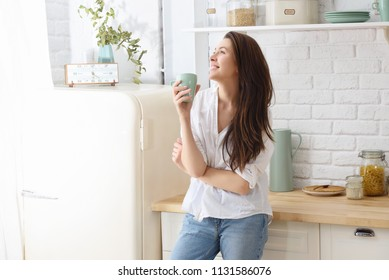 Young happy woman drinking coffee on the kitchen in the morning.