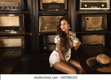 Young happy woman drinking iced coffee in stylish retro cafe with a lot of old radio