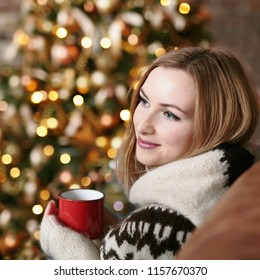 Young happy woman drinking mulled wine while sitting near decorated Christmas tree