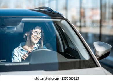 Young and happy woman driving a luxury car, front view through the windshield with sunlight