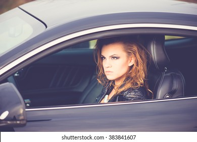 Young happy woman driving a sport car