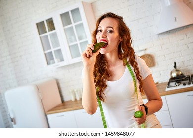 Young happy woman eating cucumber for making salad in the beautiful kitchen with green fresh ingredients indoors. Healthy food and Dieting concept. Loosing Weight