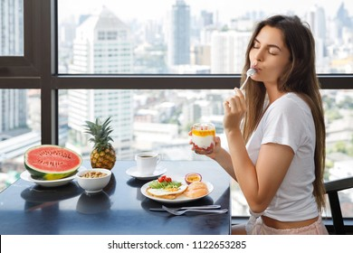Young and happy woman is eating fresh yoghurt with a passion fruit for breakfast