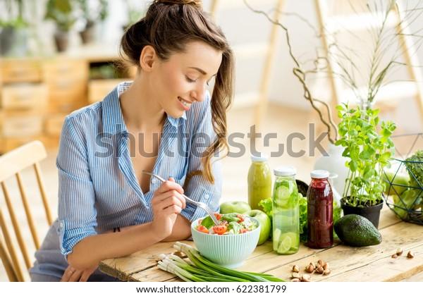 Mujer joven y feliz comiendo ensalada sana sentada en la mesa con ingredientes frescos verdes en el interior