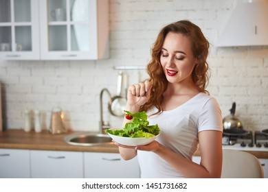 Young happy woman eating salad in the beautiful kitchen with green fresh ingredients indoors. Healthy food concept