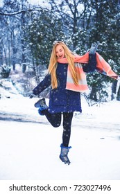 Young happy woman enjoy snow in winter city park outdoor. Happy teen girl walking outside