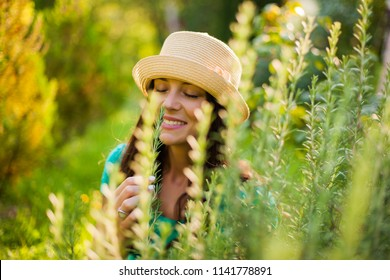 Young happy woman is enjoying the smell of rosemary in her garden.