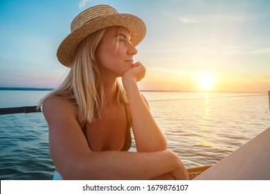 Young happy woman enjoying sunset from deck of sailing boat moving in sea at evening time. Travel, Summer, Holidays, Journey, Trip, Lifestyle, Yachting concept.