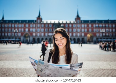 Young happy woman exploring center  of Madrid. visiting famous landmarks and places.Cheerful female traveler at famous Plaza Mayor square admiring statue of Philip III.Spain travel experience.