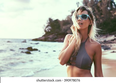 Young happy woman in fashion bikini have fun on the tropical beach in summer. Sunset sunlight, lifestyle photo.