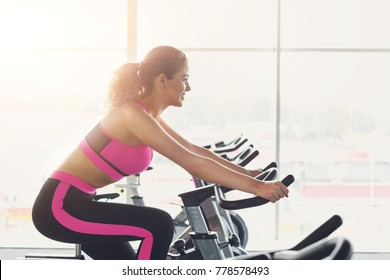 Young happy woman in fitness club. Cardio workout on stationery exercise bikes. Healthy lifestyle, training in gym. Flare effect, copy space, side view