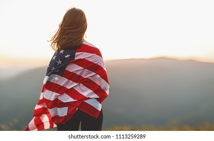 young happy woman with flag of united states enjoying the sunset on nature