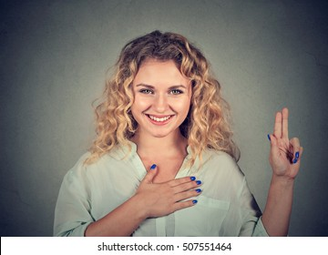 Young happy woman in glasses making a promise isolated on gray wall background