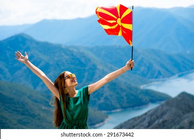 Young happy woman in green dress holding macedonian flag on the top of mountain near Kozjak lake in Macedonia. Promoting tourism in Macedonia