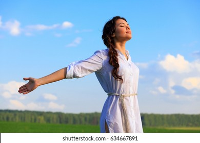 Young happy woman in green field. Green grass and blue sky behind.