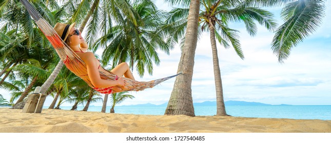 Young happy woman in hat and sunglasses laying in hammock on the tropical beach. Banner edition.
