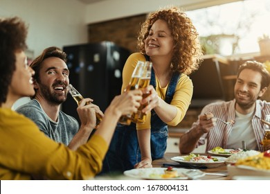 Young happy woman having fun while toasting with her friends during a lunch at dining table.