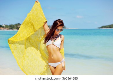 Young happy woman having fun on the beach