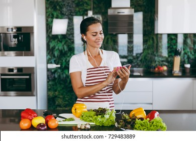 The young happy woman with headphones in the ears holding mobile phone in hands in kitchen. Vegetable salad. Diet. Dieting concept. Healthy lifestyle. Cooking at home. Prepare food