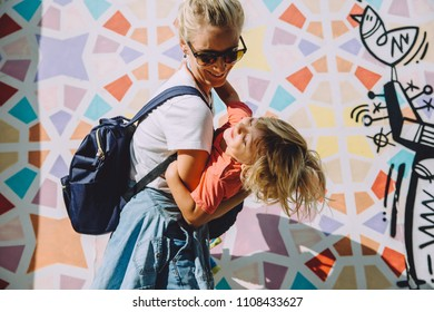 Young happy woman with her cute little son having fun against bright wall in Dubai, UAE