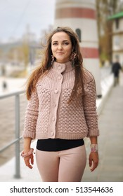 Young happy woman hike near lighthouse, happy, fresh and smiling, dressed in casual gentle pink sweater and trousers, autumn outdoor