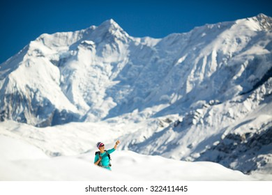 Young happy woman hiker looking at mountain peak summit in winter mountains. Climbing inspiration and motivation, beautiful landscape. Trekking healthy lifestyle outdoors on snow in Himalayas, Nepal.