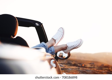 Young happy woman hipster pushes her shoes out of convertible car and admires or enjoy the view in the mountains at sunset