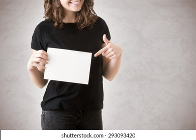Young happy woman holding a blank business card on a white background