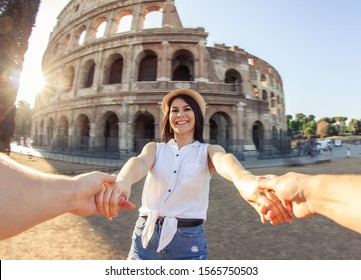Young happy woman holding boyfriend hands spinning at Colosseum. POV. Come with me. Rome, Italy
