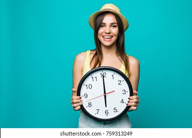 Young happy woman holding a clock with 12 clock on a green