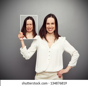 young happy woman holding her sad picture