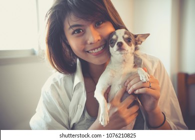 Young happy woman holding little dog in bed room with eyes stairing forward looking straight.