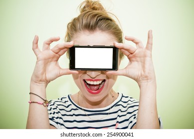 Young happy woman holding smarphone over eyes with blank white display screen. Copy space.