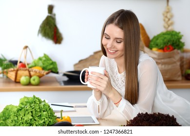 Young happy woman holding white cup and looking at the camera while sitting at wooden table in the kitchen among green vegetables. Good morning, lifestyle or cooking concept